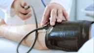 Doctor measuring blood pressure with sphygmomanometer and stethoscope video