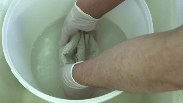 Doctor moistens elastic bandage in water standing in trauma unit video