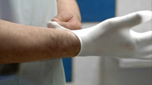 Doctor putting on white sterilized surgical glove video