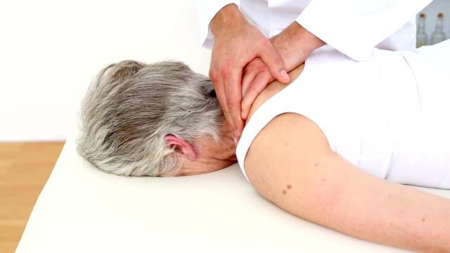 Doctor rubbing senior patients shoulders video