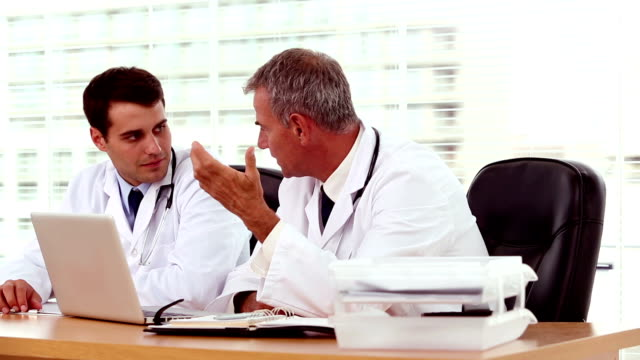 Doctor showing and explaining something to his colleague video