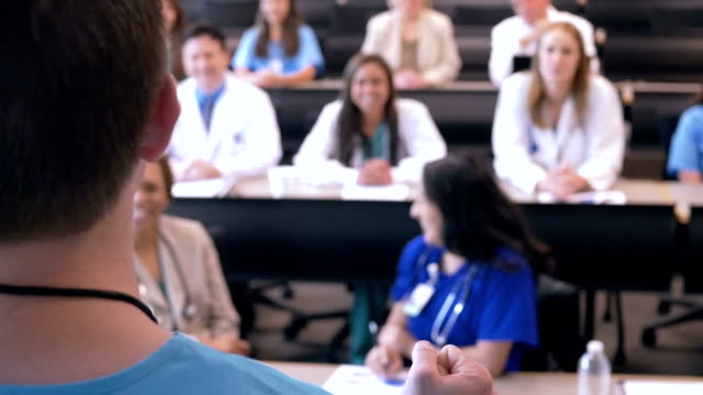 Doctor speaking to group of hospital staff during healthcare conference video