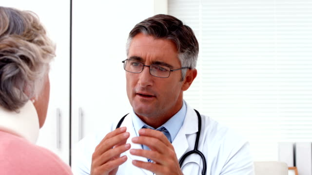 Doctor speaking with his patient at desk video