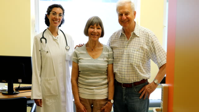 Doctor standing with senior couple at clinic video
