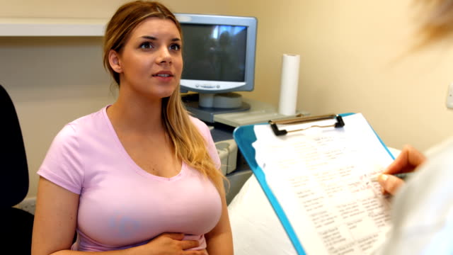 Doctor taking down notes from a pregnant patient video