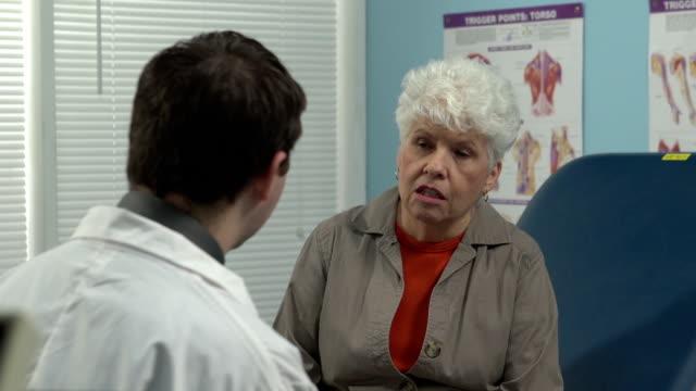 Doctor talking to concerned senior patient. video