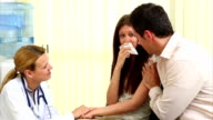 Doctor talking to crying woman in a waiting room video