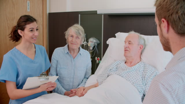 Doctor Talking To Senior Male Patient And Wife In Hospital video