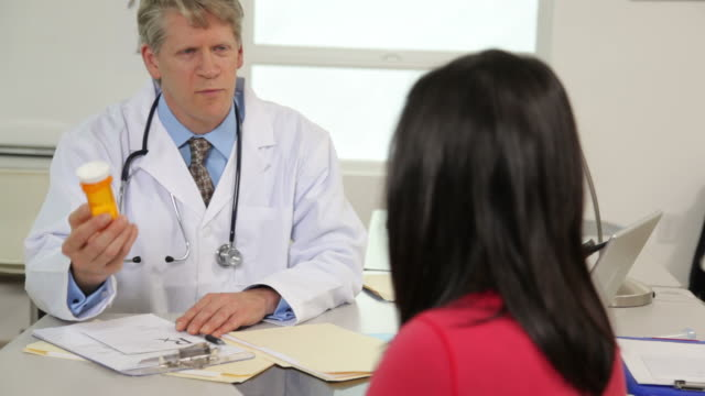 Doctor talks to patient and writes prescription video