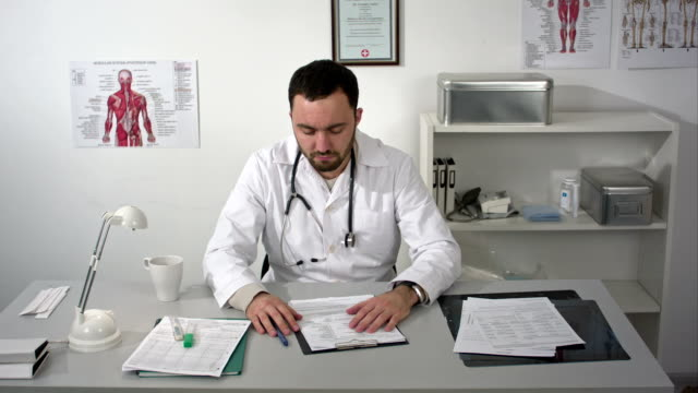 Doctor tired and holding his head at medical cabinet video