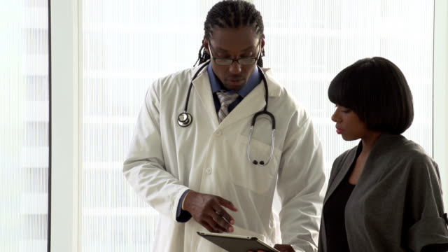 Doctor walking with patient holding tablet / ipad, close up video