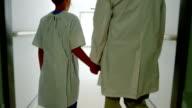 Doctor walking with patient in hospital corridor video