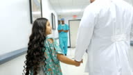 Doctor walks little girl down hospital hallway video