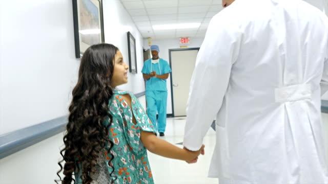 Doctor walks little girl down hospital hallway video