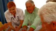 Doctor watching senior people playing cards video