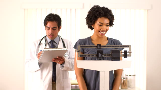 Doctor weighing African American patient video