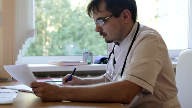 Doctor with beard and mustache in glasses is writing at the table. video
