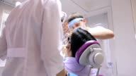 Doctor with his assistant are busy with treatment of teeth in cabinet video