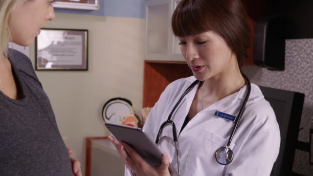 Doctor with tablet talks to pregnant patient video