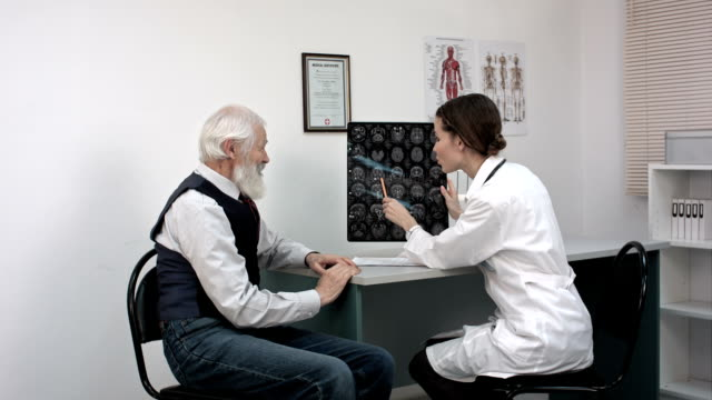 Doctor woman communicates to elder patient the good results of MRI scans video