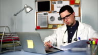 Doctor working at workplace with notebook and medical forms. video