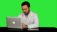 Doctor working on a laptop looking tired on a Green Screen, Chroma Key video