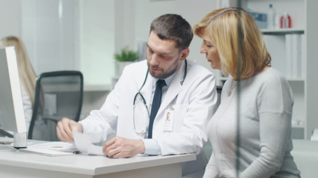 Doctor Writes Prescription to his Mid Adult Female Patient. They Talk and Smile. video