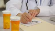 Doctor writing a prescription at desk, close up video