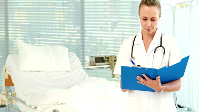 Doctor writing on clipboard and looking at camera video