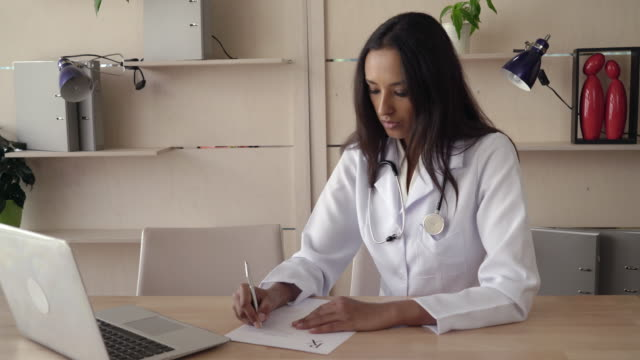 Doctor writing prescription check information on the computer video