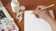 Doctor writing the result of research video