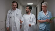 DS Doctors talking while walking down hospital hallway video