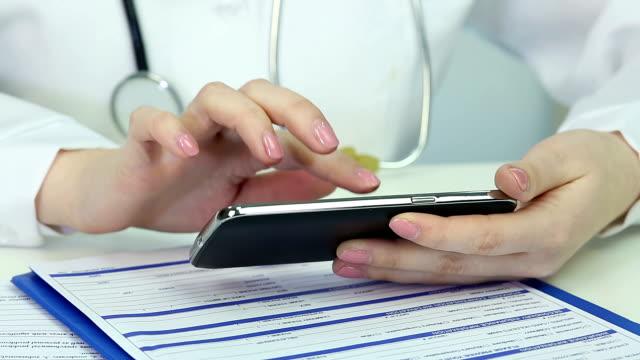 Doctor's hands sliding pages on smartphone screen, prescribing medication online video
