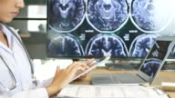 Doctor's hands using digital tablet in office video