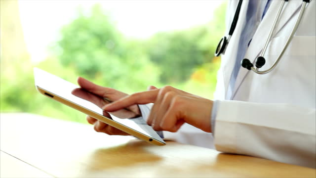 Doctor's hands using digital tablet on wooden desk video