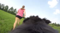 POV Dog and female owner running and playing in meadow video