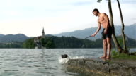 Dog tries to grab stick and fall in to lake video