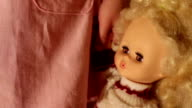 Doll in a girl's hands closeup video
