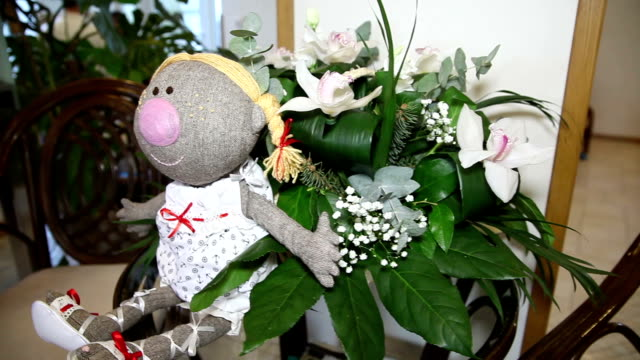 Doll with flowers on the table video