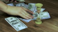 Dollar Banknotes Falling on a Wooden Table and Hourglass video
