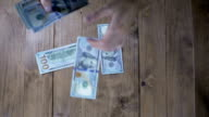 Dollar Banknotes Falling on a Wooden Table. Slow Motion video