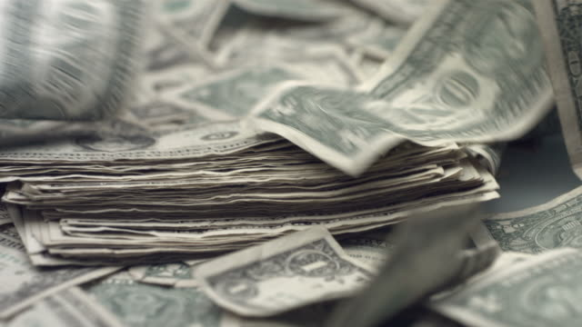 Dollar bills blowing away, slow motion video