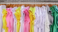 Dolly: Colorful t-shirts on hangers in a clothing store video