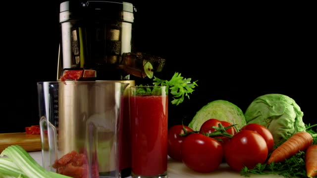 Dolly: Fresh squeezed tomato juice with cold press juicer on a black background video