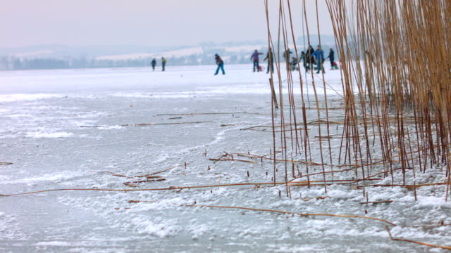 Dolly: Ice and ice skaters on a frozen lake video