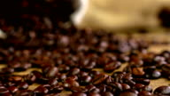 Dolly of scattered coffee beans, bag with coffee beans in the background video