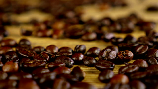 Dolly of scattered coffee beans on wooden table video