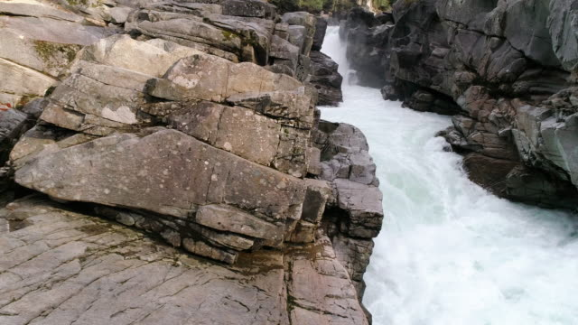 Dolly Right Across Rocky Terrain with White Water Rapids Waterfall at 60P 4K video