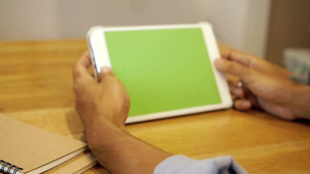 Dolly shot  -A man uses a tablet computer with green screen video