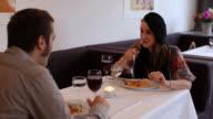 Dolly shot in restaurant, couple having dinner, mature woman leaves video